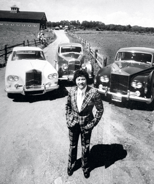 Rocky Aoki with cars he owns.